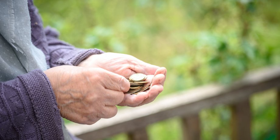 Hände eines älteren Menschen halten Münzen
