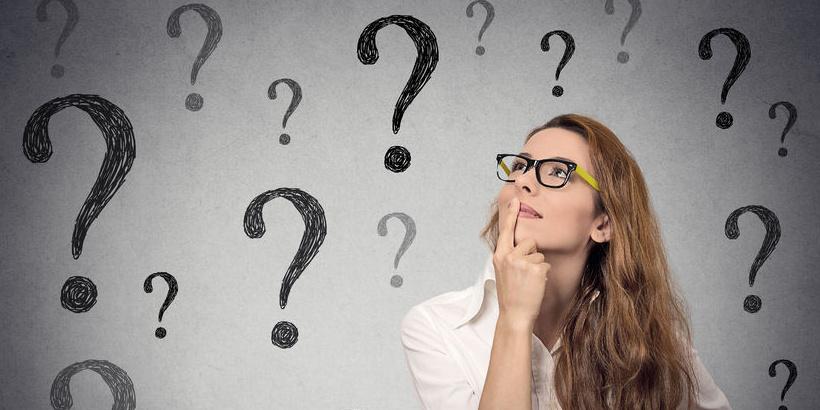 Junge Frau schsut nachdenklich auf viele Fragezeichen