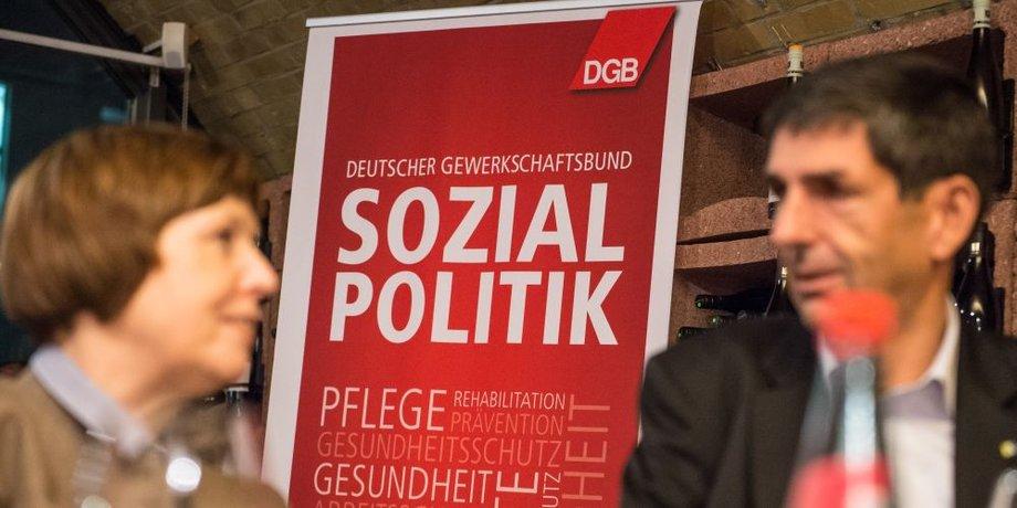 DGB Plakat mit dem Schriftzug Sozialpolitik mit zwei diskutierenden Menschen