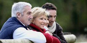 Älterer Mann, ältere Frau, jüngerer Mann, jüngere Frau lehnen an Holz-Geländer und blicken lächelnd in die Ferne