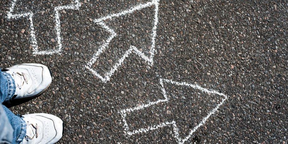 Füße in Turnschuhen stehen vor Pfeilen, die mit Kreide auf den Asphalt gemalt sind