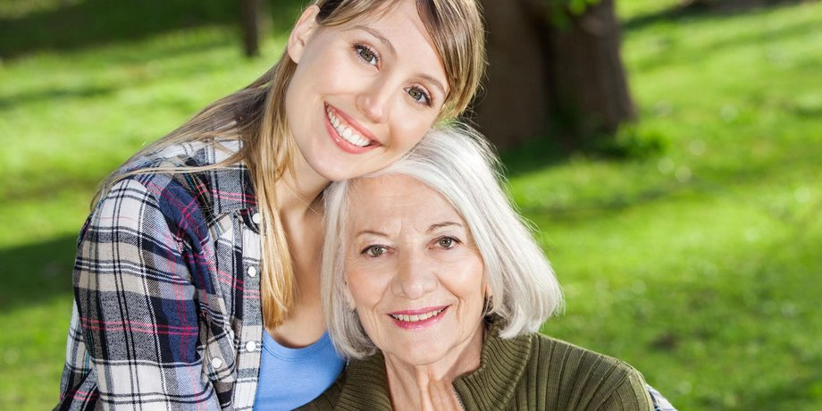 Lächelnde junge Frau umarmt lächelnde alte Frau