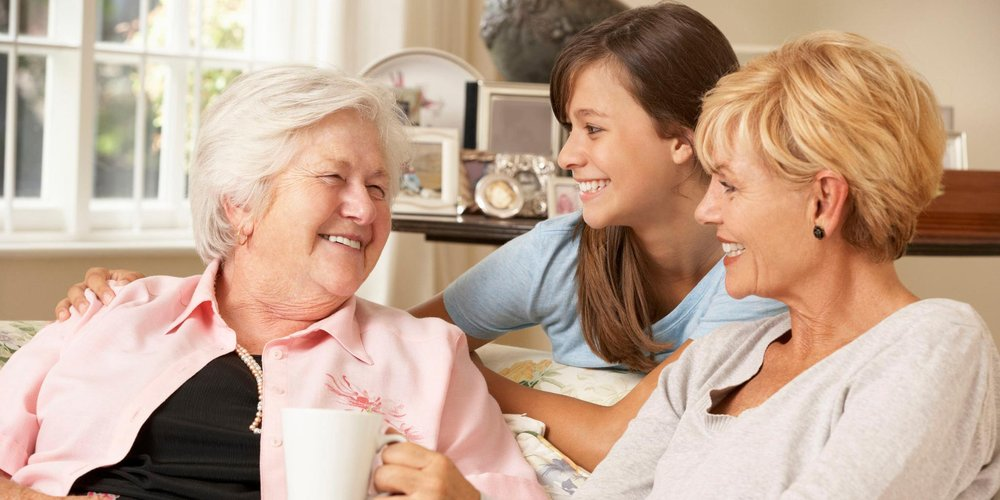 Mutter, Tochter und Enkelin sitzen zusammen auf der Couch und trinken Kaffee