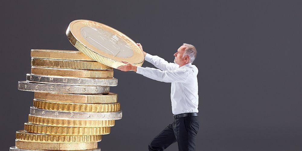 Männliche Person stapelt Münzen aufeinander